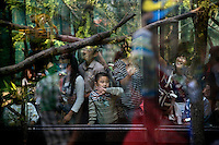 Visitors to the Beijing Zoo surround a squirrel monkey enclosure in Beijing, China.