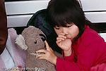 4 year old girl sucking thumb and holding favorite stuffed animal toy koala comfort habits horizontal