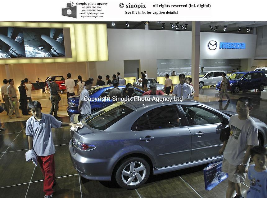 Visitors look at Mazda cars at the Auto China 2004 exhibition in Beijing, China..