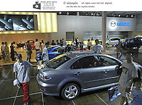 Visitors look at Mazda cars at the Auto China 2004 exhibition in Beijing, China..