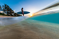A surfer girl enjoys the sunset after her surf session, North Shore, O'ahu.