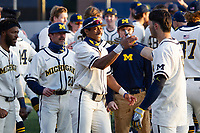 Michigan Wolverines teammates Clark Elliott (15) and Jimmy Obertop (8) celebrate their walk-off victory against the Michigan State Spartans during Big Ten NCAA baseball action at Ray Fisher Stadium on March 21st, 2021 in Ann Arbor, Michigan. Michigan scored 8 runs in the bottom of the ninth inning to win 8-7. (Andrew Woolley/Four Seam Images)