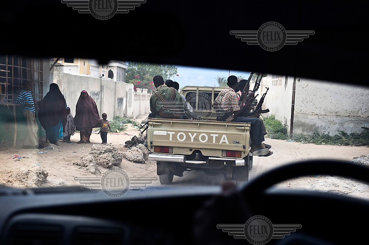 Private militia drive around the streets of Mogadishu carrying guns, seen through the windscreen of a vehicle. Although Al Shabab have been driven out of the city, security is still a problem.
