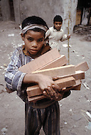 In Casablanca, Morocco, children are employed to carry various loads. Child labor as seen around the world between 1979 and 1980 - Photographer Jean Pierre Laffont, touched by the suffering of child workers, chronicled their plight in 12 countries over the course of one year.  Laffont was awarded The World Press Award and Madeline Ross Award among many others for his work.