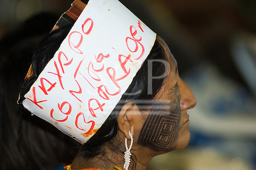 """Altamira, Brazil. """"Xingu Vivo Para Sempre"""" protest meeting about the proposed Belo Monte hydroeletric dam and other dams on the Xingu river and its tributaries. Kayapo woman wearing a cardboard headband with """"Kayapo Contra Barragem"""" written on it."""