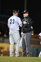 Field umpire Blake Carnahan talks with manager Brian Schneider (23) after ejecting third baseman Ross Wilson (3 - not shown) during a game between the Jupiter Hammerheads and Bradenton Marauders on April 17, 2014 at McKechnie Field in Bradenton, Florida.  Bradenton defeated Jupiter 2-1.  (Mike Janes/Four Seam Images)
