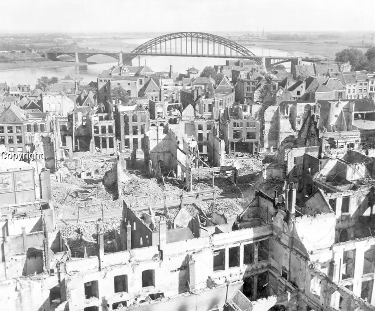 A panoramic view of the city of Nijmegen, Holland, and the Nijmegen Bridge over the Waal (Rhine) River in the background.  The city was hit by German and Allied bombardment and shelling.  September 28, 1944. Poznak. (Army)<br /> NARA FILE #:  111-SC-194568<br /> WAR & CONFLICT BOOK #:  1067