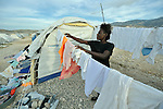 Lorette Beauvoit hangs clean laundry to dry on a clothesline in front of her tent. She is one of thousands of survivors of the devastating January 2010 earthquake who today lives in the Corail resettlement camp north of Port-au-Prince, Haiti. Residents of the camp were relocated to the remote location from overcrowded tent cities for the homeless in the nation's capital. Yet shortly after its establishment, homeless families from around the capital region moved to the area and began constructing their simple homes around the edges of the official camp, creating a complex set of questions for camp managers. The United Methodist Committee on Relief, a member of the ACT Alliance, has built schools in the camp and is providing school furniture, teacher training, and educational materials for students.
