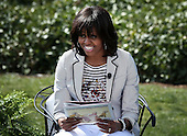 """First lady Michelle Obama reads the story """"Cloudy with a Chance of Meatballs"""" to children during the annual White House Easter Egg Roll on the South Lawn of the White House April 1, 2013 in Washington, DC.  President Barack Obama and first lady Michelle Obama hosted thousands of people during the annual celebration of Easter.  .Credit: Alex Wong / Pool via CNP"""