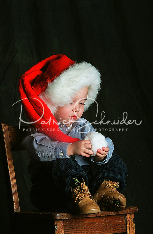 A young boy plays with the Santa hat on his head during a photo shoot.