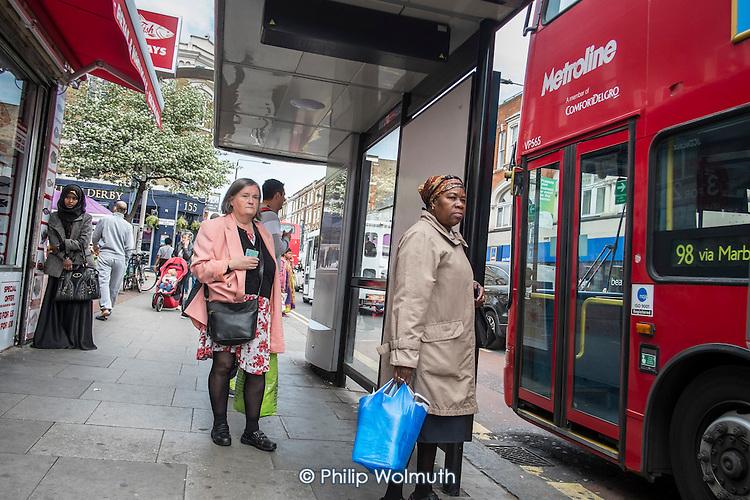 Waiting at a bus-stop, Kilburn, London.