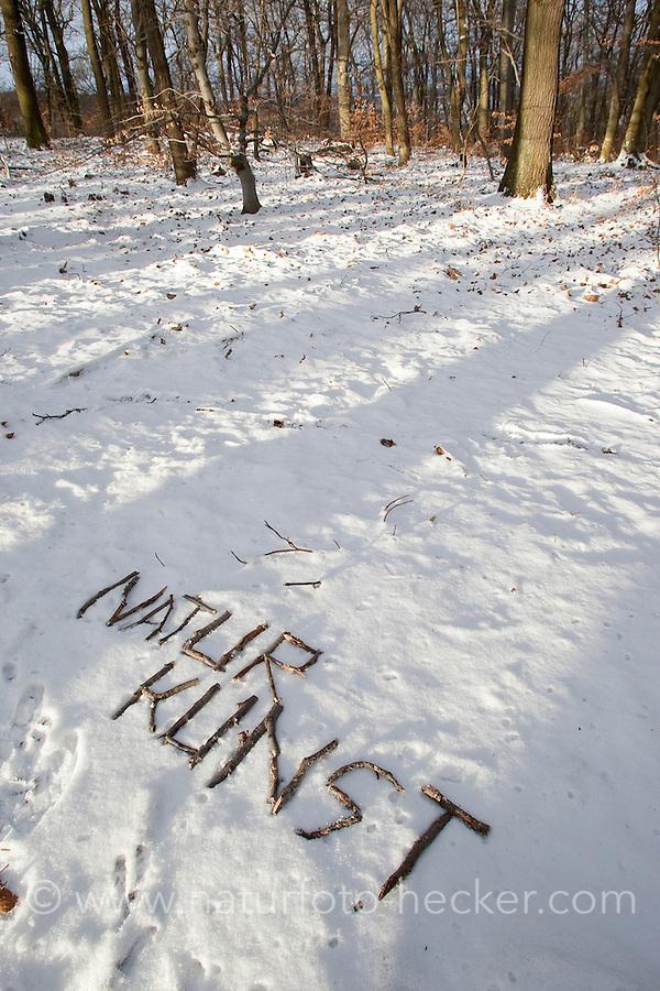 """Naturkunst im Winter, Kind schreibt das Wort """"Naturkunst"""" mit Stöckchen in den Schnee"""