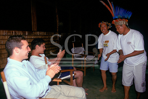 Tataquara, Brazil. Yaimo (Francisco) Waiwai in feather headdress and Joe Waiwai playing and singing at the tourist hotel.