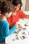 Education preschool 3-4 year olds female teacher working on number concepts with boy using cards showing numerals and butterfly counters