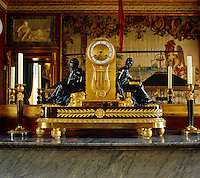 On the marble mantelpiece of the billard room an elegant ormolu clock is flanked by a pair of matching candlesticks