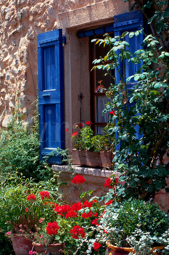 Picturesque exterior decor of blue shutters, flowers and vines growing on an old stone building. France.