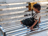 A child looking at her reflection at a bench at the entrance of the Kuthodaw Pagoda & the World's Largest Book, Mandalay<br />