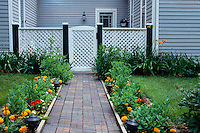 path to garden at side of house with gate and fence bordered by blooming flowers