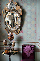 An embellished mirror, deep purple upholstery and antiquities combine to create a style that is bold and sophisticated.