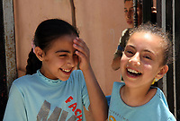 """Gaza.June.09.2008.Aya Masouad 8 years born without arms,use here toes and feet to go around with her daily life,she payling with her sister in her house. she easts or drink with her toes , she love her life and thanking God, she practice her life as she is normel people . """" Photo by Thair Alhassany/propaimages"""""""