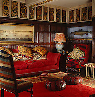 A carved gilt-frieze with a variety of crests runs around the ceiling of this wood-panelled sitting room