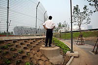 """CHINA. Beijing. A man peers through a fence, trying to catch a glimpse of the new Olympic park. In recent years construction has boomed in Beijing as a result of the country's widespread economic growth and the awarding of the 2008 Summer Olympics to the city. For Beijing's residents however, it seems as their city is continually under construction with old neighborhoods regularly being razed and new apartments, office blocks and sports venues appearing in their place. A new Beijing has been promised to the people to act as a showcase to the world for the 'new' China. Beijing's residents have been waiting for this promised change for years and are still waiting, asking the question """"Where's the new Beijing?!"""". 2008"""