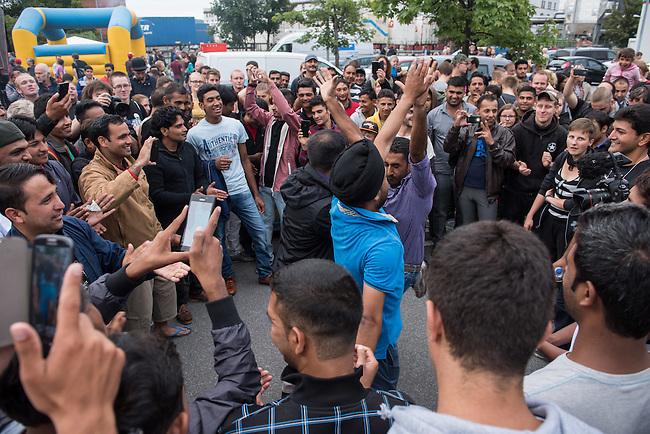 Wilkommensfest fuer Fluechtlinge im saechsichen Heidenau.<br /> Nachdem Polizei und politisch Verantwortliche vergeblich versucht hatten ein Wilkommensfest fuer Fluechtlinge mit dem Argument des Polizeilichen Notstands zu verbieten feierten hunderte Menschen zusammen. Fuer die Fluechtlinge waren Kleidungs- und Sachspenden nach Heidenau gebracht worden, die in Berlin, Dresden und anderswo gesammelt wurden.<br /> Zahlreiche Polizeikraefte waren zum Schutz des Festes im Einsatz.<br /> Im Bild: Fluechtlinge aus Syrien, Afghanistan und anderen Laendern musizieren, singen und tanzen zusammen mit deutschen Fluechtlingsaktivisten.<br /> 28.8.2015, Heidenau<br /> Copyright: Christian-Ditsch.de<br /> [Inhaltsveraendernde Manipulation des Fotos nur nach ausdruecklicher Genehmigung des Fotografen. Vereinbarungen ueber Abtretung von Persoenlichkeitsrechten/Model Release der abgebildeten Person/Personen liegen nicht vor. NO MODEL RELEASE! Nur fuer Redaktionelle Zwecke. Don't publish without copyright Christian-Ditsch.de, Veroeffentlichung nur mit Fotografennennung, sowie gegen Honorar, MwSt. und Beleg. Konto: I N G - D i B a, IBAN DE58500105175400192269, BIC INGDDEFFXXX, Kontakt: post@christian-ditsch.de<br /> Bei der Bearbeitung der Dateiinformationen darf die Urheberkennzeichnung in den EXIF- und  IPTC-Daten nicht entfernt werden, diese sind in digitalen Medien nach §95c UrhG rechtlich geschuetzt. Der Urhebervermerk wird gemaess §13 UrhG verlangt.]