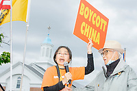 """Bao Chau Kelley holds a sign reading """"Boycott China"""" as she speaks to the crowd as people gather for an anti-lockdown protest organized by the alt-right group Super Happy Fun America near the home of Massachusetts governor Charlie Baker in Swampscott, Massachusetts, on Sat., May 16, 2020. The protest was in defiance of Massachusetts orders mandating face coverings and social distancing and prohibiting gatherings larger than 10 people during the ongoing Coronavirus (COVID-19) global pandemic. The state's stay-at-home order is expected to be updated on May 18, 2020, with a phased reopening plan issued by the governor as COVID-19 cases continue to decrease. Anti-lockdown protests such as this have become a conservative cause and have been celebrated by US president Donald Trump. Many of the protestors displayed pro-Trump messages or wore Trump campaign hats and shirts with phrases including """"Trump 2020"""" and """"Keep America Great."""" Super Happy Fun America, organizers of the protest, are an alt-right organization best known for creating the 2019 Boston Straight Pride Parade."""