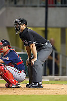 Home plate umpire Derek Millica sets up behind Gwinnett Braves catcher Jose Yepez (25) during the game against the Charlotte Knights at BB&T Ballpark on August 19, 2014 in Charlotte, North Carolina.  The Braves defeated the Knights 10-5.   (Brian Westerholt/Four Seam Images)