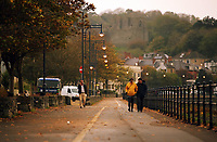 """Pictured: A couple stroll during an unusually dark morning by the seaside village of Mumbles near Swansea, UK. Monday 16 October 2017<br />Re: Remnants of Hurricane Ophelia are expected to bring strong gusts of wind to Wales when it hits Britain's shores.<br />The hurricane, making its way from the Azores in the Atlantic Ocean, will have weakened to a storm when it arrives.<br />A Met Office amber """"be prepared"""" warning has been issued in some areas bringing """"potential danger to life""""."""