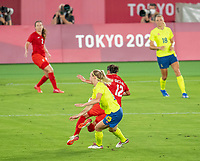 YOKOHAMA, JAPAN - AUGUST 6: Christine Sinclair #12 of Canada is fouled by Amanda Ilestedt #13 of Sweden during a game between Canada and Sweden at International Stadium Yokohama on August 6, 2021 in Yokohama, Japan.