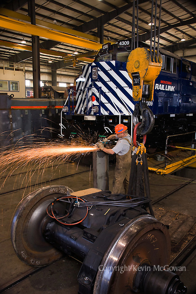 Welder at train engine repair factory, wheel assembly in foreground