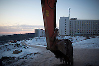 An earthmover stands at rest near new residential building construction in Ufa, Bashkortostan, Russia.