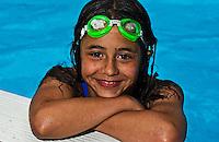 Girl (9-10)smiles at edge of pool