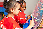 Education Preschool art activity two girls painting at easel sharing paper