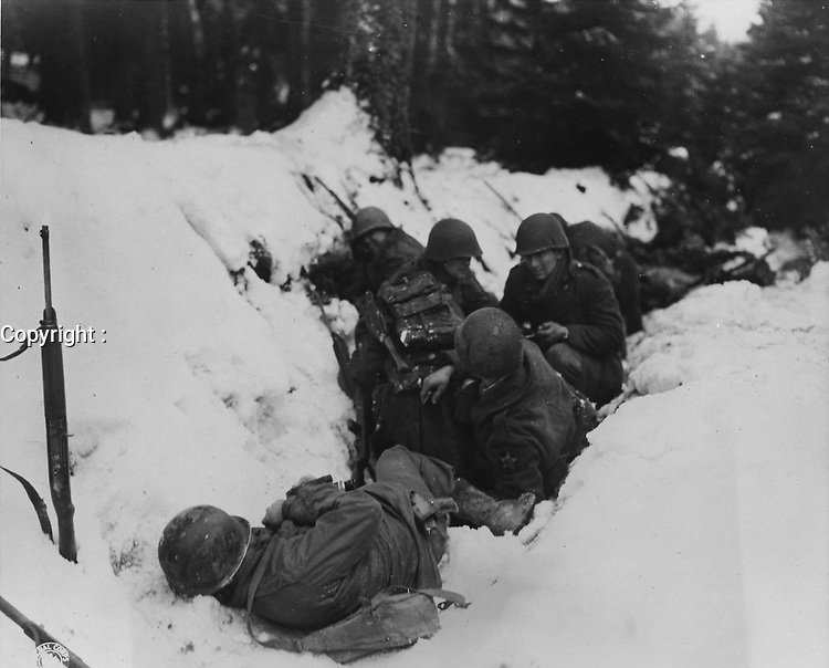 U.S. infantrymen of the 9th Infantry Regiment, 2nd Infantry Division, First U.S. Army, crouch in a snow-filled ditch, taking shelter from a German artillery barrage during the Battle of Heartbreak Crossroads in the Krinkelter woods on 14 December 1944.