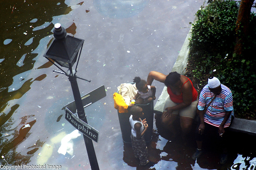 A family takes a break from wading through water in New Orleans after Hurricane Katrina, New Orleans, August 31, 2005..
