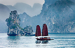 Vietnam's Ha Long Bay is one of the most dramatic landscapes in all of southeast Asia. Karst mountains and rocky pinnacles rise dramatically out of the bay.  The unusual shape of the sails of the fishing craft complete the monochromatic scene.