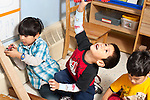 Education preschool 3-4 year olds three boys playing separately with wooden blocks and vehicles