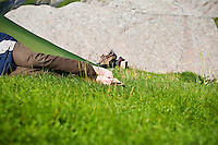 Person takes nap in sunny weather outside tent, Lofoten islands, Norway