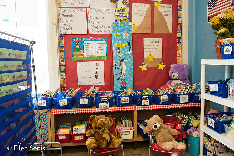 MR / Schenectady, New York. Yates Arts-in-Education Magnet School (urban public school). First grade classroom. Attractive reading area in early childhood classroom includes books, chairs, stuffed animals, and a bulletin board. MR: AM-g1w. ID: AM-g1w. © Ellen B. Senisi.