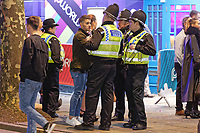Pictured: A police officers speak to a male reveller in Wind Street, Swansea. Monday 31 December 2018 and Tuesday 01 January 2019<br /> Re: New Year revellers in Wind Street, Swansea, Wales, UK
