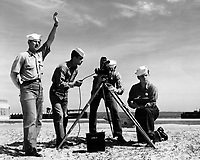 Students at Naval School of Photography working on a practical outdoor assignment, Class 4 (Movies).  Instructor C.R. Greenwalt, PhoM 1/c, with hand raised is supervising students at work on the Eyemo Model Q 35 mm motion picture camera with electric motor drive.