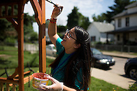 """Judy Nguyen applies stain to a gazebo during """"Circle the City with Service,"""" the Kiwanis Circle K International's 2015 Large Scale Service Project, on Wednesday, June 24, 2015, in Indianapolis. (Photo by James Brosher)"""