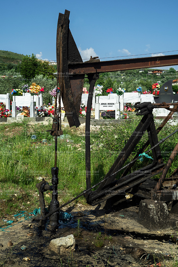 Albania. Kucova. Oil derrick in a graveyard. Working oil pump among the tombs. Tombs and and plastic flowers used for decoration. A derrick is a lifting device composed at minimum of one guyed mast, as in a gin pole, which may be articulated over a load by adjusting its guys. Most derricks have at least two components, either a guyed mast or self-supporting tower, and a boom hinged at its base to provide articulation, as in a stiffleg derrick. Kucova is a village in Vlorë County. 25.05.2018 © 2018 Didier Ruef