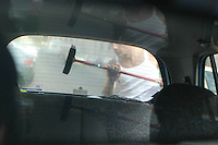 Immigrato mentre lava i vetri di un automobile ai semafori. .Immigrant while washing the windows of a car near the traffic lights..