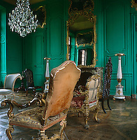 The Green Salon has boiserie painted a startling green and is furnished with an assortment of single chairs including a pair of gilded Louis XV Revival chairs in the foreground