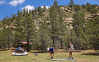 Photo story of Philmont Scout Ranch in Cimarron, New Mexico, taken during a Boy Scout Troop backpack trip in the summer of 2013. Photo is part of a comprehensive picture package which shows in-depth photography of a BSA Ventures crew on a trek.  In this photo BSA Venture Crew Scouts work together to setup their tent at the base of the mountains in Dean Cow Camp, in the backcountry at Philmont Scout Ranch.   <br /> <br /> The  Photo by travel photograph: PatrickschneiderPhoto.com