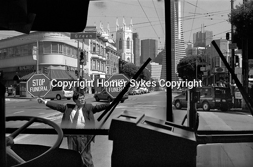 Funeral in progress man holding up a Stop Funeral sign, San Francisco California USA 1999. 1990s taken from inside of a Greyhound bus.