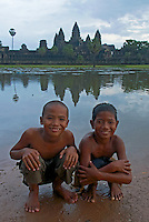 Two boys in front of Angkor Wat taken a bath in the water of the moat surrounding the temple. Angkor Wat, Cambodia